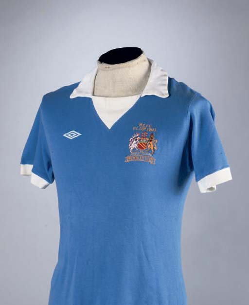 A BLUE MANCHESTER CITY SHORT-SLEEVED 1976 LEAGUE CUP FINAL SHIRT No.9, with v-neck collar and embroidered badge, inscribed M.C.F.C., F.L. Cup Final, Wembley 1976 . The shirt is an official spare example produced for the Final. In the above League Cup Final played on 28 February 1976 at Wembley, Manchester City defeated Newcastle United 2-1. The No.9 shirt was worn by Joe Royle