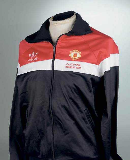 A RED, BLACK AND WHITE MANCHESTER UNITED F.A. CUP FINAL TRACKSUIT TOP with embroidered badge, inscribed Manchester United Football Club, F.A. Cup Final, Wembley 1983  In the above F.A. Cup Final played on 21st May 1983 at Wembley, Manchester United drew 2-2 with Brighton and Hove Albion. In the Replay played on 26th May 1983 at Wembley, United defeated Brighton 4-0. The above top was worn for the first Final