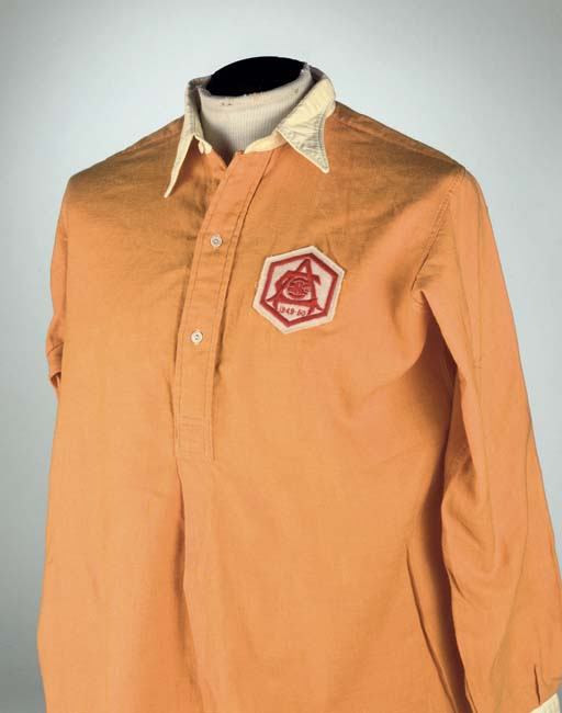 AN ORANGE ARSENAL 1950 F.A.CUP FINAL SHIRT No.6, with button-up collar and embroidered cloth badge, inscribed 1949-50 Provenance Fred Grosvenor and thence by family descent Exhibited Arsenal Football Club Museum, Highbury Lot Notes The above shirt was worn by Arsenal Captain Joe Mercer in the 1950 F.A.Cup Final. In the match played on 29th April 1950 at Wembley Arsenal defeated Liverpool 2-0. The shirt was gifted to the Arsenal physiotherapist and kit man Fred Grosvenor by Joe Mercer Please