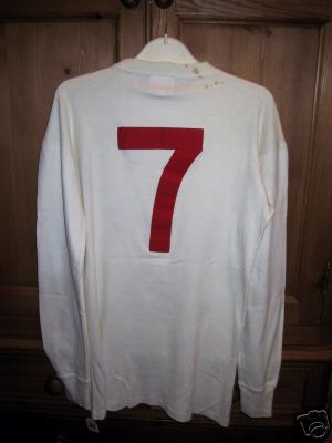 It is a white round collared Umbro no 7 number shirt.
