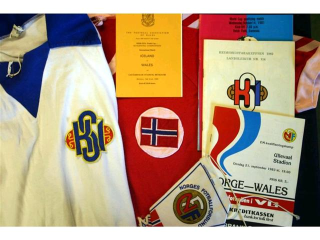 321. International Shirts Etc: A white with blue trim Iceland International Shirt with embroidered badge to front, No. 7 to rear plus itinerary, pin badge, programmes & ceramic tankard relating the match against Wales played in Reykjavik 2nd June 1980 (Giles scored in this match); also a red with white trim V-neck Norway shirt with embroidered badge to front, No.7 to rear plus programme & pennant relating to the match played in Oslo 21st September 1983. £120-150