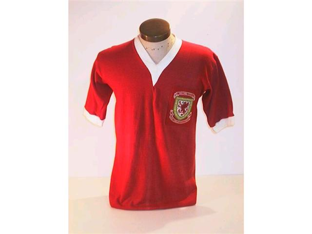 457. Wales International Shirt: A red with white trim V-neck shirt with embroidered Welsh crest to front with the match details above, No. 10 to rear. Illus. £500-700