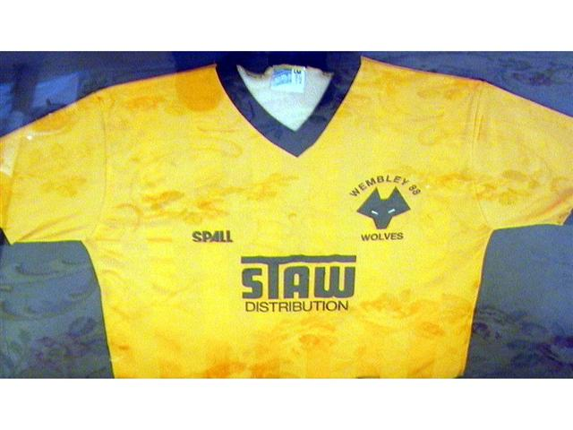 459. Shirt: An old gold with black trim V-neck shirt, Wolverhampton Wanderers crest to front with 'Wembley 88' above and sponsors 'Staw Distribution' below. Mounted, framed and glazed. Illus. £500-600