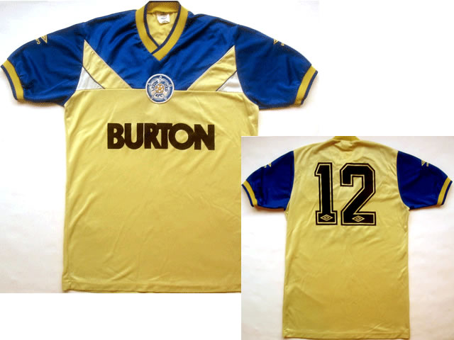 Embroidered Umbro logos, stitched club badge, heat pressed Umbro players No.12. The first Leeds shirt to bear the classic Burton sponsor, worn when Billy Bremner was manager